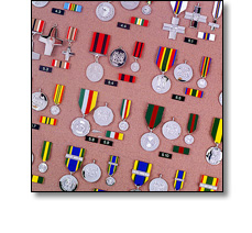 Many military medals on a short ribbons, and ribbon bars